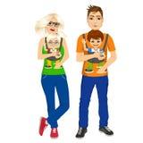 Γονείς που κρατούν το κράτημα των παιδιών τους με το φορέα μωρών Στοκ φωτογραφία με δικαίωμα ελεύθερης χρήσης