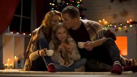 Γονείς που φιλούν την κόρη, που πίνει το καυτό κακάο κοντά στο χριστουγεννιάτικο δέντρο, εορταστική ατμόσφαιρα στοκ εικόνα
