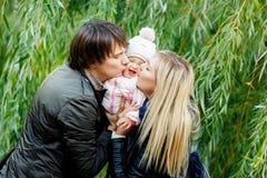 Γονείς που φιλούν την κόρη μωρών γύρω από τα δέντρα στο πάρκο Στοκ εικόνες με δικαίωμα ελεύθερης χρήσης