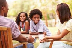 Γονείς που χαλαρώνουν ενώ τα παιδιά παίζουν στον κήπο Στοκ Εικόνα