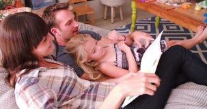 Γονείς που χαλαρώνουν στο βιβλίο ανάγνωσης εδρών στην κόρη φιλμ μικρού μήκους