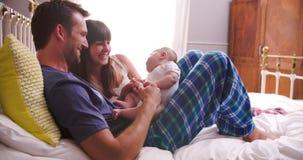 Γονείς στο παιχνίδι κρεβατιών με τη νεογέννητη κόρη μωρών απόθεμα βίντεο