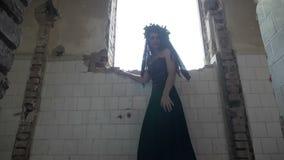 Γοτθική γυναίκα που παγιδεύεται στο συχνασμένο κτήριο που φαίνεται έξω το παράθυρο και που κρύβει από τα φαντάσματα φιλμ μικρού μήκους