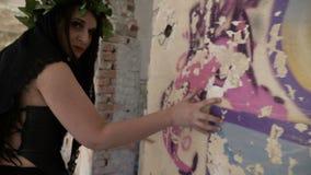 Γοτθικό κορίτσι που αγγίζει και που ακούει ο τοίχος σε ένα δωμάτιο σε αναζήτηση των φαντασμάτων φιλμ μικρού μήκους