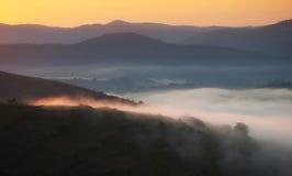 Γούρνα ομίχλης οι λόφοι και τα λιβάδια στην ανατολή Στοκ εικόνα με δικαίωμα ελεύθερης χρήσης