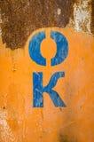 Γράμματα ΕΝΤΑΞΕΙ ν διάτρητων μια σκουριασμένη επιφάνεια Στοκ Φωτογραφίες
