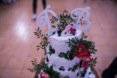 Γράμμα Δ γαμήλιων διακοσμήσεων & Β στο όμορφο άσπρο γαμήλιο κέικ με τα ρόδινες λουλούδια και την πρασινάδα Στοκ Εικόνα