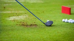 Γράμμα Τ παικτών γκολφ από τη σφαίρα γκολφ πριν από την ταλάντευση στοκ φωτογραφία