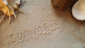 Γράφει το καλοκαίρι λέξης, στην άμμο της παραλίας με ένα θαλασσινό κοχύλι και μια καρύδα Στοκ Φωτογραφία