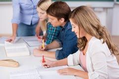 Γράφοντας γυναίκα σπουδαστής με τους συμμαθητές στο γραφείο στοκ φωτογραφία