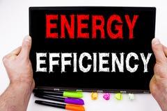 Γράψιμο παρουσιάζοντας ενεργειακή αποδοτικότητα που γίνεται στο γραφείο με τη μάνδρα δεικτών lap-top περιχώρων Επιχειρησιακή έννο Στοκ Εικόνες