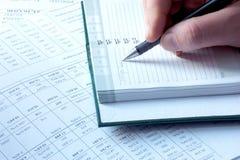 Γράψιμο στις φορολογικές οδηγίες σημειωματάριων στοκ φωτογραφία με δικαίωμα ελεύθερης χρήσης