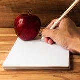 Γράψιμο χεριών και φρέσκο μήλο Στοκ φωτογραφία με δικαίωμα ελεύθερης χρήσης