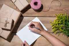 Γράψιμο χεριών που επιθυμεί με το δώρο γενεθλίων στο ξύλινο υπόβαθρο VI Στοκ Φωτογραφίες