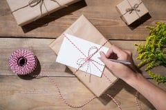 Γράψιμο χεριών που επιθυμεί με το δώρο γενεθλίων στο ξύλινο υπόβαθρο VI Στοκ εικόνα με δικαίωμα ελεύθερης χρήσης