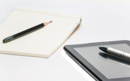 Γράψτε κάτω σε χαρτί από το μολύβι και το νέο τρόπο στην ταμπλέτα Στοκ εικόνα με δικαίωμα ελεύθερης χρήσης