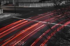 Γρήγορα κινούμενη κυκλοφορία με τα ίχνη κόκκινου φωτός στο μαύρο δρόμο Στοκ Φωτογραφία