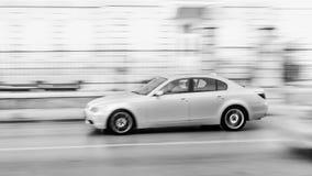 Γρήγορα κινούμενο αυτοκίνητο στο οδόστρωμα πόλεων στη θαμπάδα κινήσεων Στοκ Φωτογραφίες