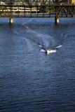 Γρήγορες ταχύτητες βαρκών μηχανών μέσω του σκοτεινού νερού της ποταμοπλοΐας κάτω από drawbridge πέρα από τον ποταμό Willamette στ στοκ φωτογραφίες