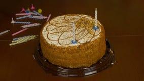 Γρήγορη επίδραση κινήσεων Τα αρσενικά χέρια διακοσμούν το κέικ με τα κεριά Επανδρώνει το χέρι παρεμβάλλει ένα ριγωτό χρωματισμένο φιλμ μικρού μήκους