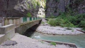 Γρήγορη ροή του ποταμού βουνών κάτω από την παλαιά αυτόματη γέφυρα στην Αμπχαζία απόθεμα βίντεο