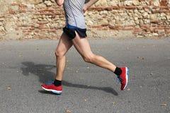 Γρήγορος δρομέας που τρέχει γρήγορα με από τα κόκκινα παπούτσια γυμναστικής στην άσφαλτο ro Στοκ φωτογραφία με δικαίωμα ελεύθερης χρήσης