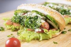 Γρήγορο εύγευστο χοτ-ντογκ άχρηστου φαγητού με τη juicy πρασινάδα και bbq λουκάνικο στον πίνακα κοντά στην ντομάτα κερασιών στοκ φωτογραφία με δικαίωμα ελεύθερης χρήσης
