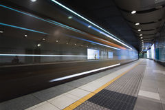 Γρήγορο τραίνο που ταξιδεύει μέσω του υπόγειου σταθμού μετρό Στοκ Φωτογραφία