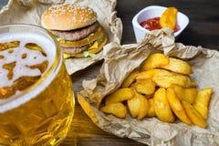 Γρήγορο φαγητό και ένα κατεψυγμένο ποτήρι της φρέσκιας ελαφριάς μπύρας Στοκ Εικόνες