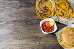 Γρήγορο φαγητό και ένα κατεψυγμένο ποτήρι της φρέσκιας ελαφριάς μπύρας Στοκ Φωτογραφίες