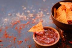 Γρήγορο φαγητό παλιοπραγμάτων που τρώει την εμβύθιση σάλτσας ντοματών τσιπ nacho Στοκ Φωτογραφίες