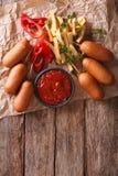Γρήγορο φαγητό: Σκυλιά, τηγανιτές πατάτες και κέτσαπ καλαμποκιού κάθετη κορυφή vie Στοκ εικόνα με δικαίωμα ελεύθερης χρήσης