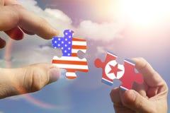 Γρίφοι υπό μορφή σημαιών της Βόρεια Κορέας και οι Ηνωμένες Πολιτείες της Αμερικής στα χέρια Στοκ Εικόνα