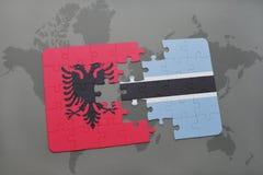 γρίφος με τη εθνική σημαία της Αλβανίας και της Μποτσουάνα σε έναν παγκόσμιο χάρτη Στοκ Εικόνες