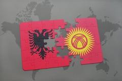 γρίφος με τη εθνική σημαία της Αλβανίας και του Κιργιζιστάν σε έναν παγκόσμιο χάρτη Στοκ φωτογραφία με δικαίωμα ελεύθερης χρήσης