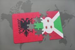 γρίφος με τη εθνική σημαία της Αλβανίας και του Μπουρούντι σε έναν παγκόσμιο χάρτη Στοκ Φωτογραφίες