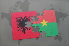 γρίφος με τη εθνική σημαία της Αλβανίας και του Burkina Faso σε έναν παγκόσμιο χάρτη Στοκ Εικόνες