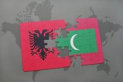γρίφος με τη εθνική σημαία της Αλβανίας και των Μαλβίδων σε έναν παγκόσμιο χάρτη Στοκ εικόνα με δικαίωμα ελεύθερης χρήσης