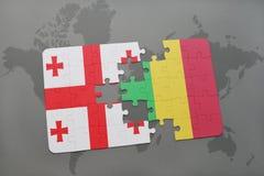 γρίφος με τη εθνική σημαία της Γεωργίας και του Μαλί σε έναν παγκόσμιο χάρτη Στοκ φωτογραφία με δικαίωμα ελεύθερης χρήσης