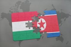 γρίφος με τη εθνική σημαία της Ουγγαρίας και της Βόρεια Κορέας σε έναν παγκόσμιο χάρτη Στοκ φωτογραφία με δικαίωμα ελεύθερης χρήσης