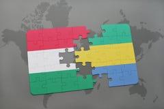 γρίφος με τη εθνική σημαία της Ουγγαρίας και της Γκαμπόν σε έναν παγκόσμιο χάρτη Στοκ Εικόνα