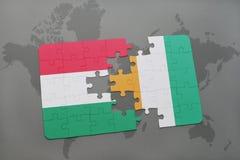 γρίφος με τη εθνική σημαία της Ουγγαρίας και του υπόστεγου divoire σε έναν παγκόσμιο χάρτη Στοκ Εικόνες