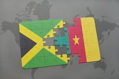 γρίφος με τη εθνική σημαία της Τζαμάικας και του Καμερούν σε έναν παγκόσμιο χάρτη Στοκ εικόνες με δικαίωμα ελεύθερης χρήσης