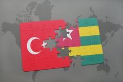 γρίφος με τη εθνική σημαία της Τουρκίας και του Τόγκο σε έναν παγκόσμιο χάρτη Στοκ εικόνες με δικαίωμα ελεύθερης χρήσης