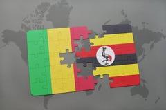 γρίφος με τη εθνική σημαία του Μαλί και της Ουγκάντας σε έναν παγκόσμιο χάρτη Στοκ φωτογραφία με δικαίωμα ελεύθερης χρήσης