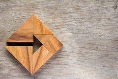 Γρίφος τανγκράμ ως βέλος στην τετραγωνική μορφή στο ξύλινο κοβάλτιο υποβάθρου στοκ φωτογραφία με δικαίωμα ελεύθερης χρήσης