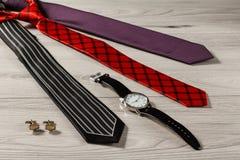 Γραβάτες μεταξιού χρώματος, ρολόι, μανικετόκουμπα σε ένα γκρίζο ξύλινο backgrou Στοκ Φωτογραφία