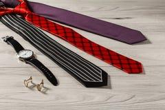 Γραβάτες μεταξιού χρώματος, wristwatch, μανικετόκουμπα σε μια γκρίζα ξύλινη ΤΣΕ Στοκ εικόνες με δικαίωμα ελεύθερης χρήσης