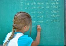 Γραμμές γραψίματος κοριτσιών στον πίνακα κιμωλίας Στοκ Φωτογραφίες