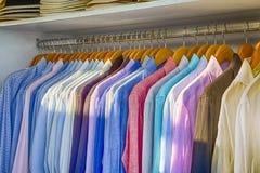 29b7fcc0474f Γραμμή ζωηρόχρωμων πουκάμισων θερινών μακριών μανικιών λινού που  τοποθετούνται στις κρεμάστρες στο κατάστημα Oia του χωριού